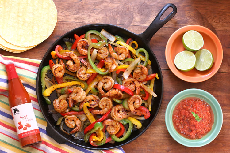 easy shrimp fajitas on a skillet next to lime slices and salsa