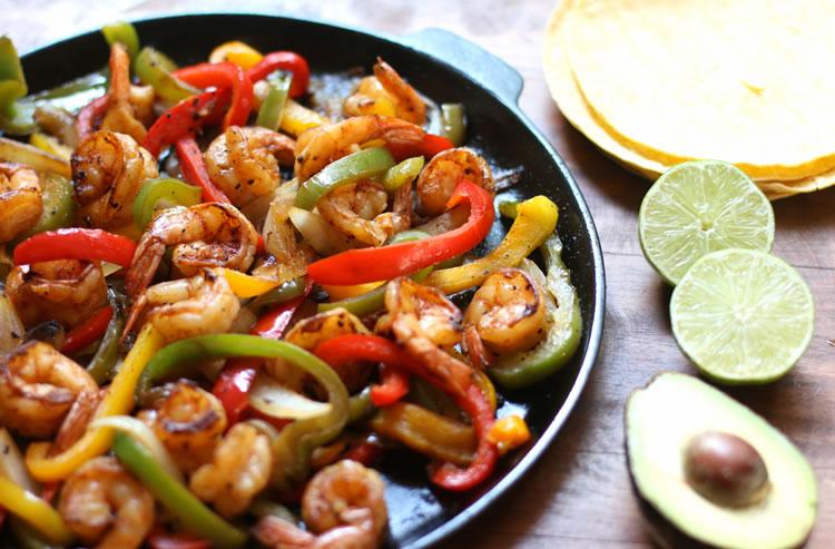 Easy Low Carb Shrimp Fajitas on a skillet next to lime and avocado