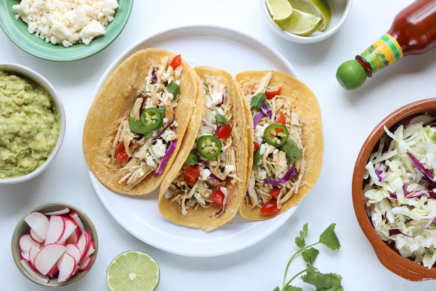 20 Minute Green Chile Chicken Tacos on a plate with cheese tomato cabbage