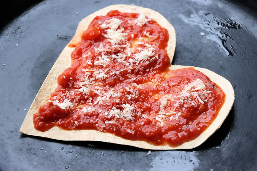 low carb heart shaped crust topped with sauce and parmesan cheese