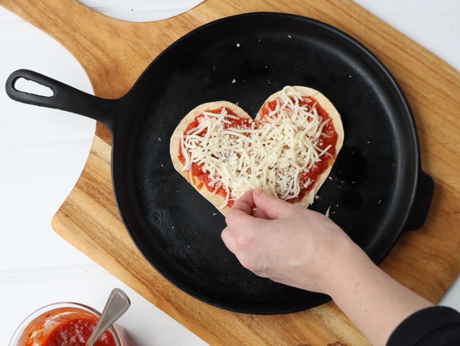 putting shredded mozzarella on a tortilla pizza on a skillet