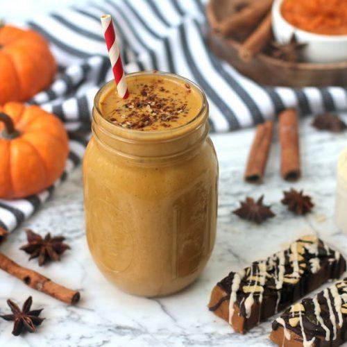 pumpkin pie protein shake in a mason jar next to pumpkin protein bar on marble next to mini pumpkins