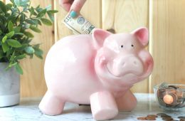 putting money in a pink piggy bank http://www.onbetterliving.com