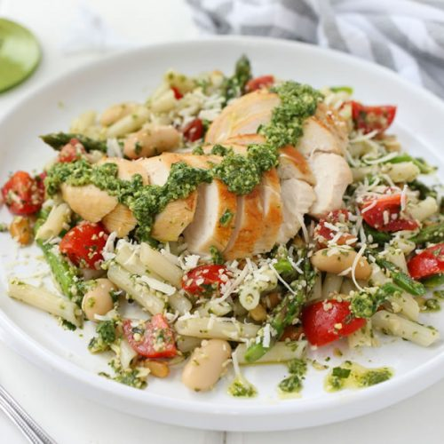 A plate of Gluten -Free Chicken Basil Pesto Pasta with a fork, gray and white striped napkin