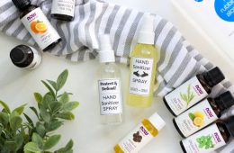 DIY Hand Sanitizers displayed next to essential oils of orange tea tree lemon and peppermint
