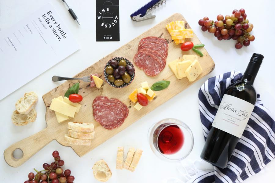 Une bouteille de cabernet Martin Ray sur une serviette rayée bleu marine de Wine Access à côté d'une planche à fromage et à viande avec des olives et des raisins