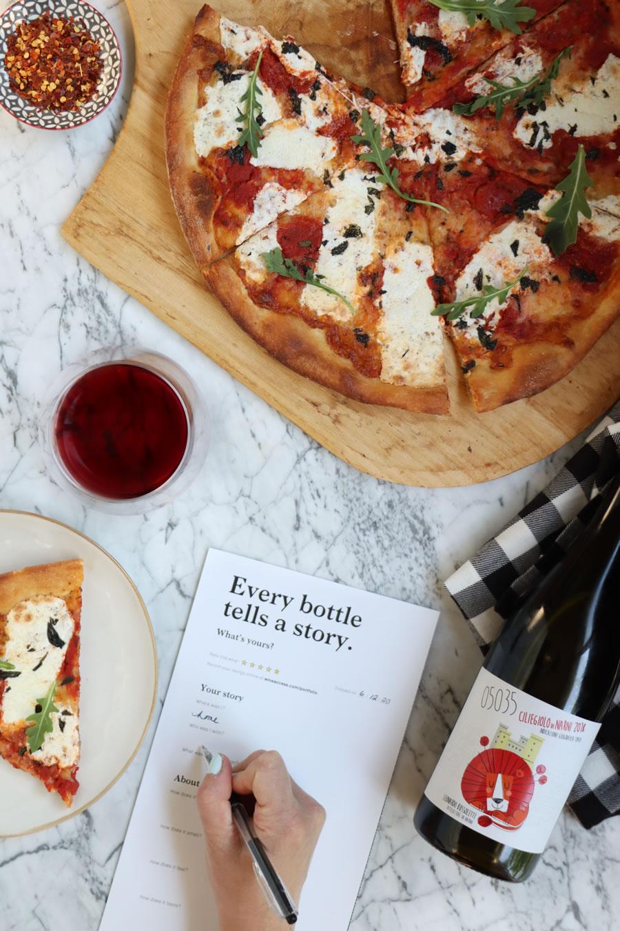 une main remplissant une carte de dégustation de vin et examinant l'accès au vin à côté de la pizza, un verre de vin et une bouteille