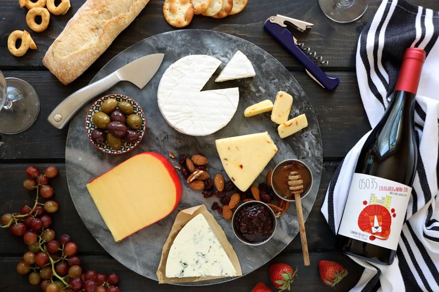 une planche à fromage en ardoise ronde à côté d'une bouteille de Ciliegiolo Narni 05035