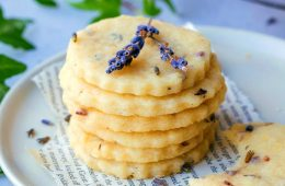 a stack of 6 buttery lavender shortbread cookies on a plate with lavender sprigs