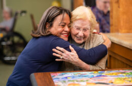People hugging at a memory care facility